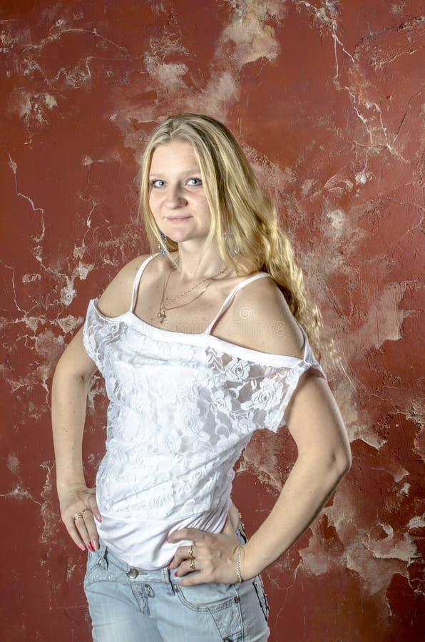Młoda blond dziewczyna w cajgach i białym pulowerze obrazy royalty free