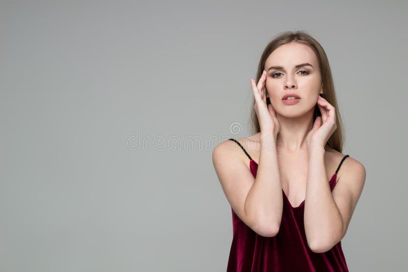 Młoda blond dziewczyna w zmroku - czerwieni suknia pokazuje emocje: rozmarzenie fotografia stock