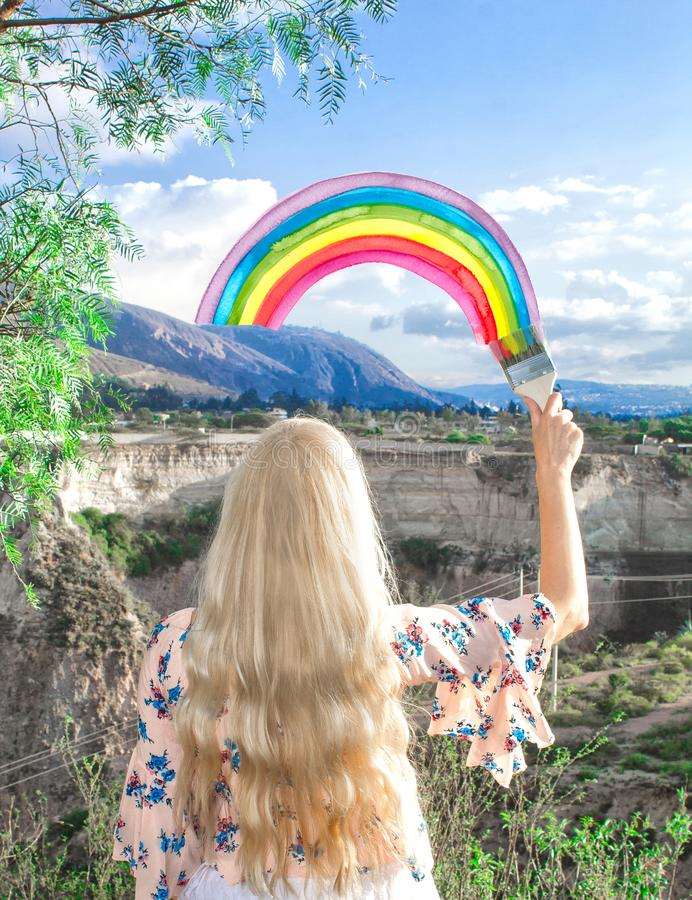 Młoda blond kobieta rysuje tęczę na niebie obraz stock