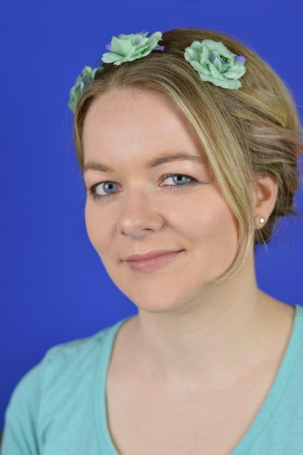 Młoda blond kobieta z updo włosy i cyan kwiatami obrazy royalty free