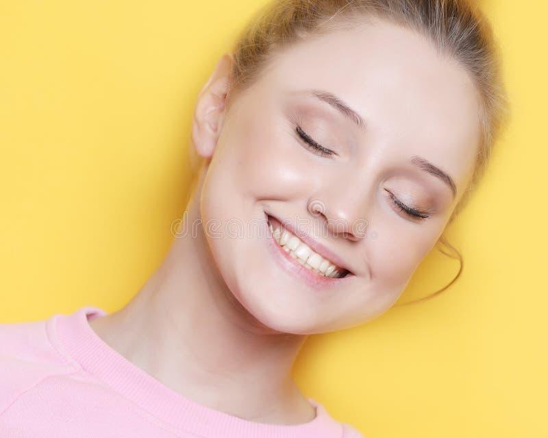 Młoda blond kobieta z zamkniętymi oczami nad żółtym tłem, obraz royalty free