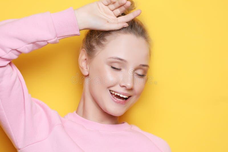 Młoda blond kobieta z zamkniętymi oczami nad żółtym tłem, zdjęcia stock
