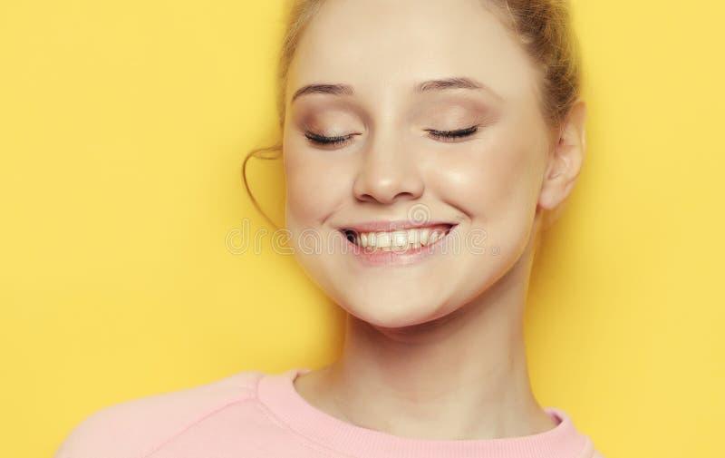 Młoda blond kobieta z zamkniętymi oczami nad żółtym tłem, obrazy royalty free