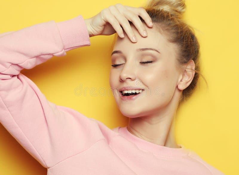 Młoda blond kobieta z zamkniętymi oczami nad żółtym tłem, zdjęcie stock