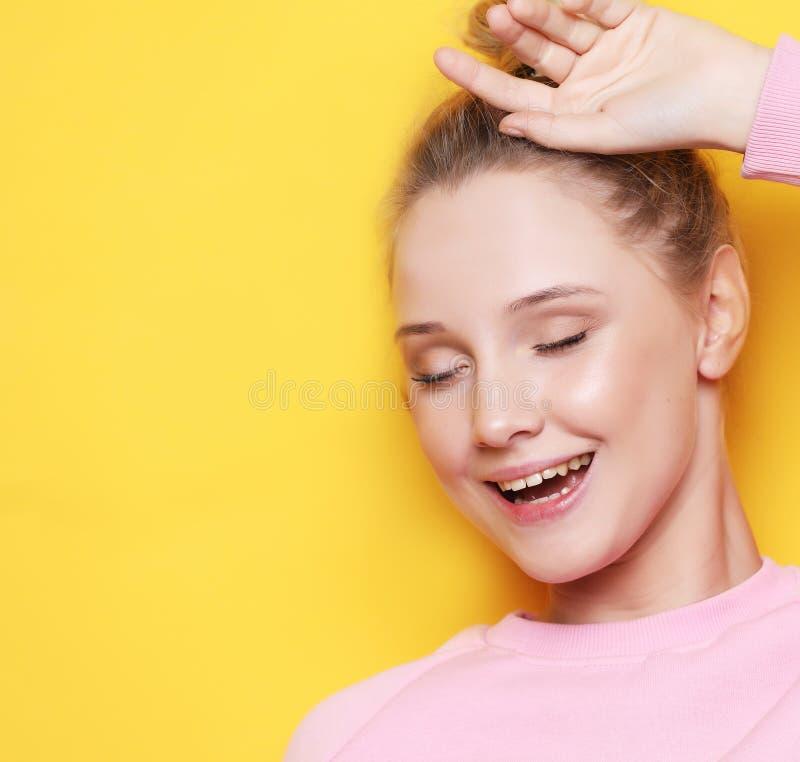 Młoda blond kobieta z zamkniętymi oczami nad żółtym tłem, fotografia stock