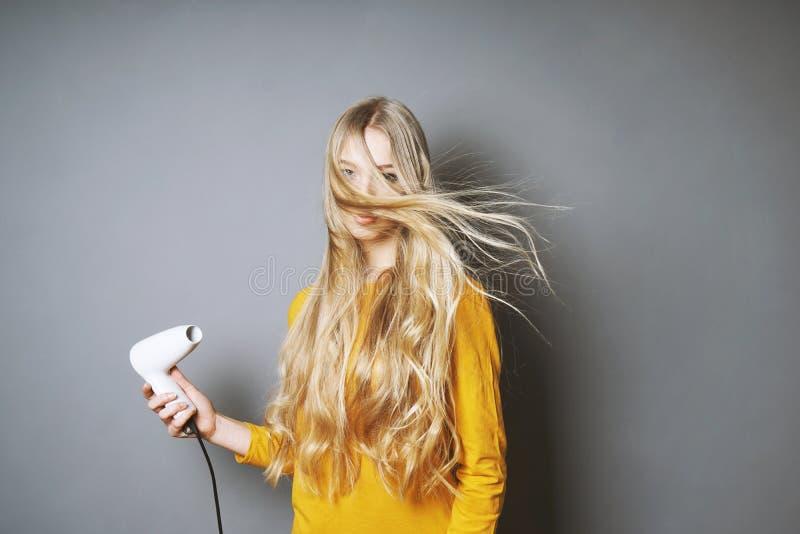 Młoda blond kobiety osuszka jej włosy zdjęcia royalty free