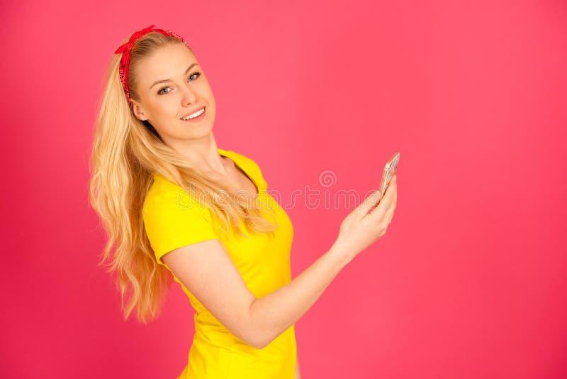 Młoda blond nastoletnia dziewczyna surfuje sieć na mądrze telefonie w żółtej t koszula obraz stock