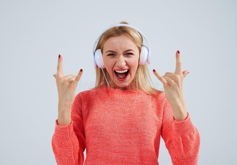 Młoda blond słuchająca muzyka rockowa w hełmofonach obraz stock