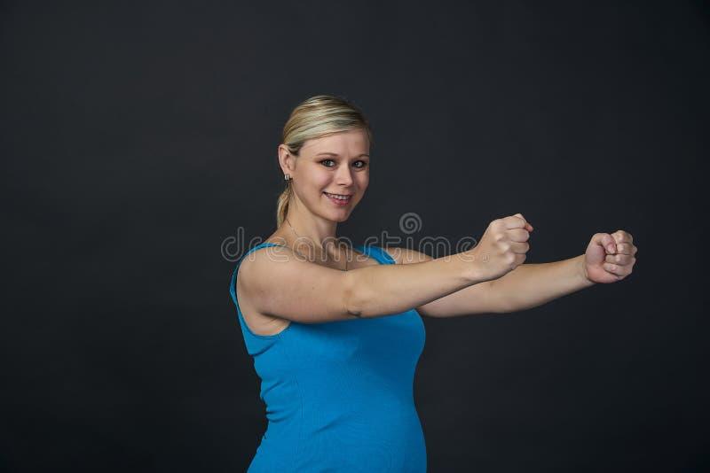 Młoda blondy kobieta w ciąży w błękitnym podkoszulek bez rękawów ćwiczenia, czarny tło fotografia stock