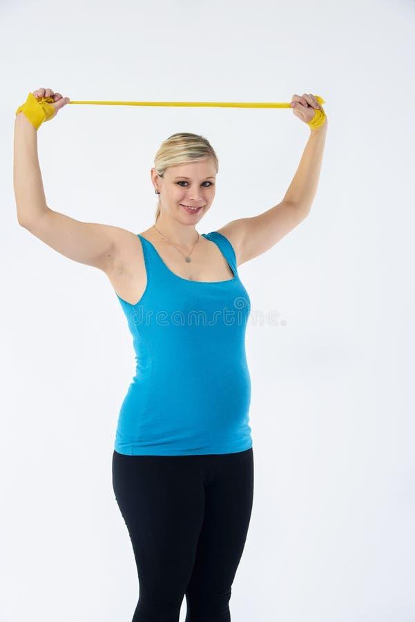 Młoda blondy kobieta w ciąży w błękitnym podkoszulek bez rękawów ćwiczenia z żółtej sprawności fizycznej gumowym zespołem, biały  obrazy royalty free
