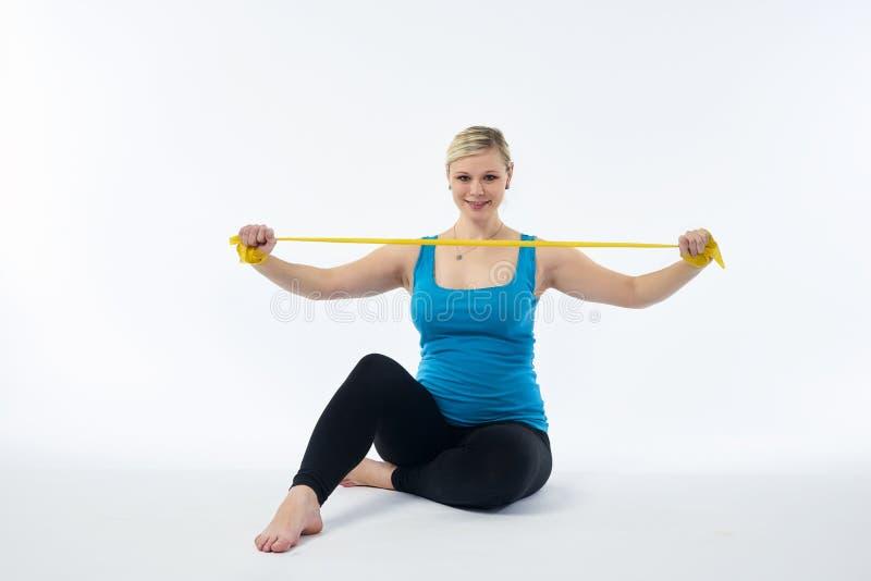 Młoda blondy kobieta w ciąży w błękitnym podkoszulek bez rękawów ćwiczenia z żółtej sprawności fizycznej gumowym zespołem, biały  zdjęcie royalty free