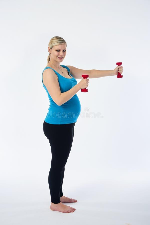 Młoda blondy kobieta w ciąży w błękitnym podkoszulek bez rękawów ćwiczenia z małymi czerwonymi sprawności fizycznych dumbbells, b zdjęcie royalty free