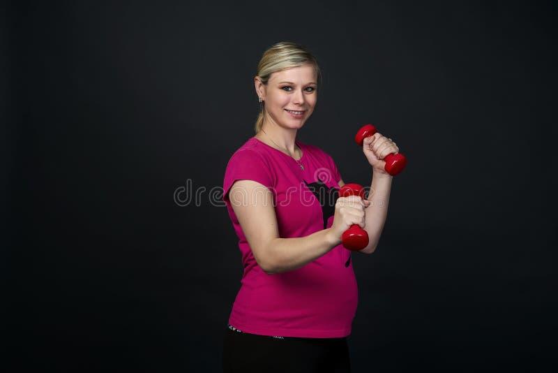 Młoda blondy kobieta w ciąży w różowym skrócie z kotem ćwiczenia z czerwonymi sprawności fizycznych dumbbells, czarny tło zdjęcia royalty free