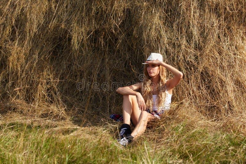 Młoda blondynka kraju dziewczyna w kapeluszowym pobliskim haystack fotografia royalty free