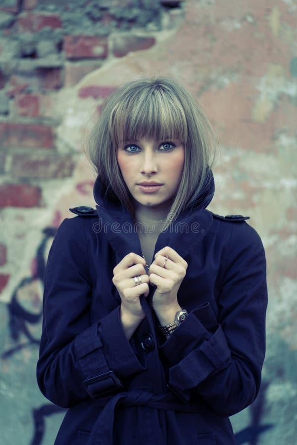 Młoda blondynka pozuje przeciw starzejącemu się ściana z cegieł zdjęcia stock