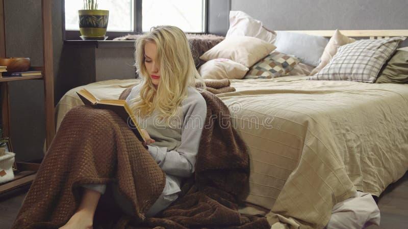 Młoda blondynka siedzi na podłoga w koc obok łóżka i czyta książkę zdjęcie stock