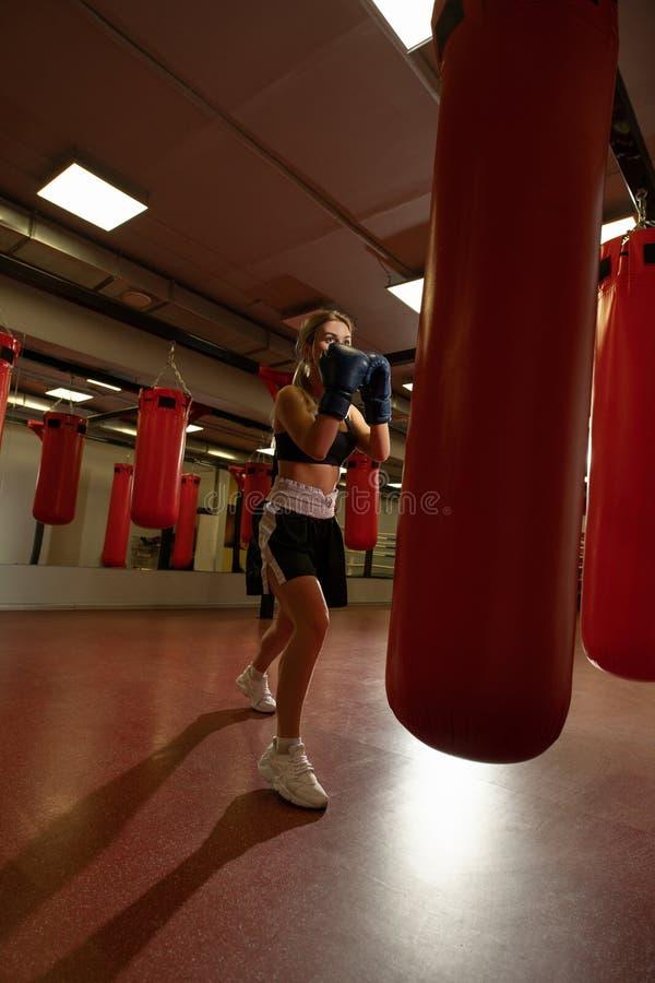 Młoda blondynka w bokserskich rękawiczkach w gym zdjęcie royalty free