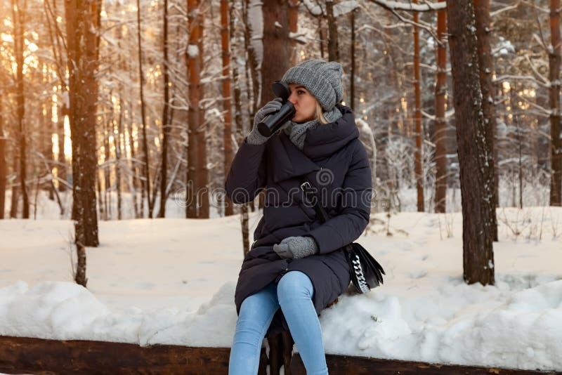 Młoda blondynka w kapeluszu, szaliku i rękawiczkach trykotowych, pije kawę lub herbaty podczas gdy siedzący na snowdrift w zimie  zdjęcie stock