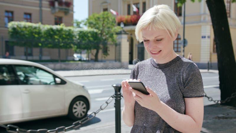 Młoda blondynki dama Używa telefon w miasteczku obraz stock