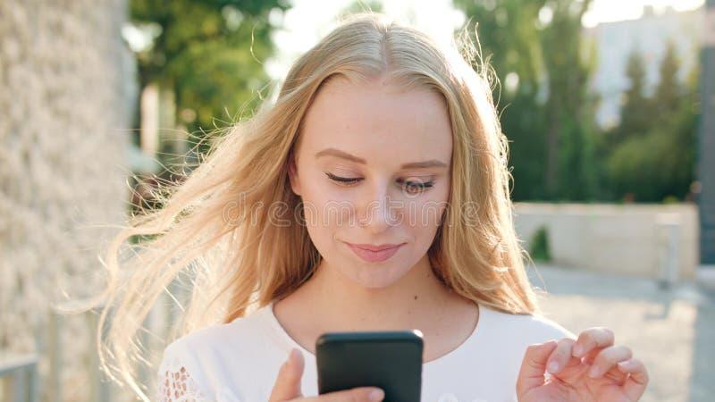 Młoda blondynki dama Używa telefon w miasteczku obraz royalty free