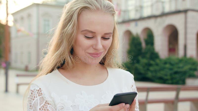 Młoda blondynki dama Używa telefon w miasteczku zdjęcie stock