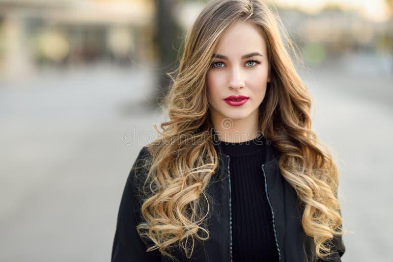 Młoda blondynki dziewczyna jest ubranym czarną kurtkę z pięknymi niebieskimi oczami zdjęcie stock