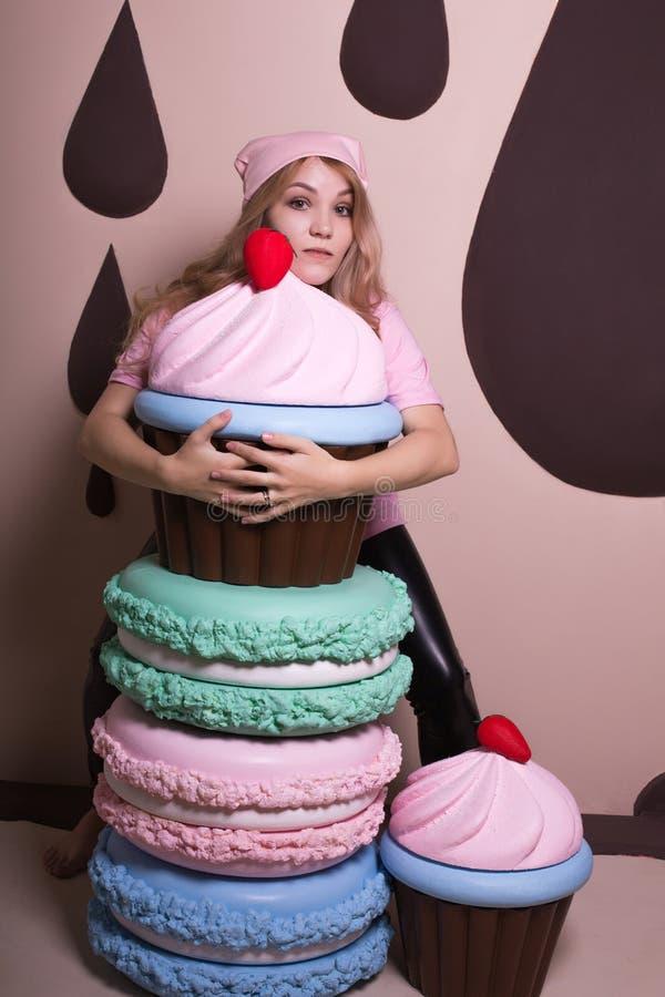 Młoda blondynki dziewczyna jest ubranym menchii nakrętkę i t koszula z ma zabawę przy studiiem dużymi babeczkami i macaroons zdjęcia stock