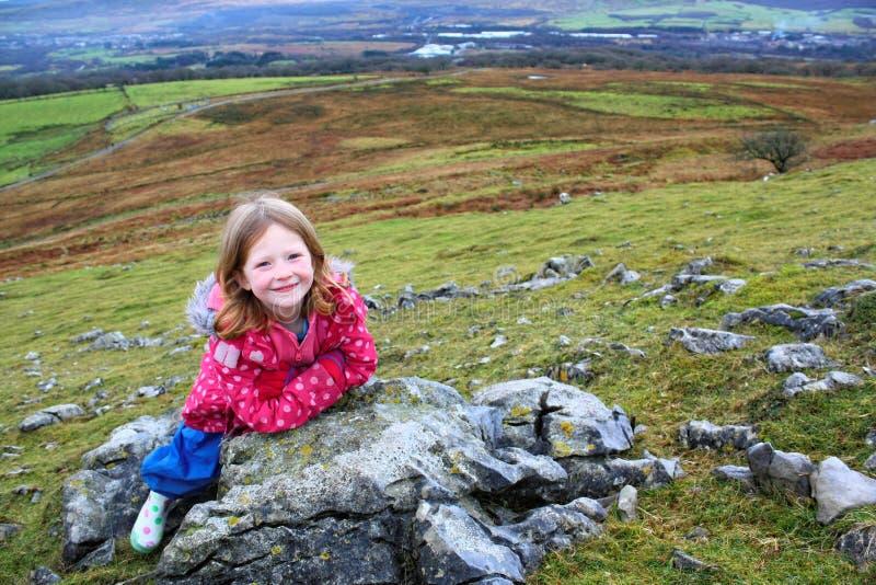 Młoda blondynki dziewczyna Odpoczywa na skałach w wzgórzach fotografia royalty free