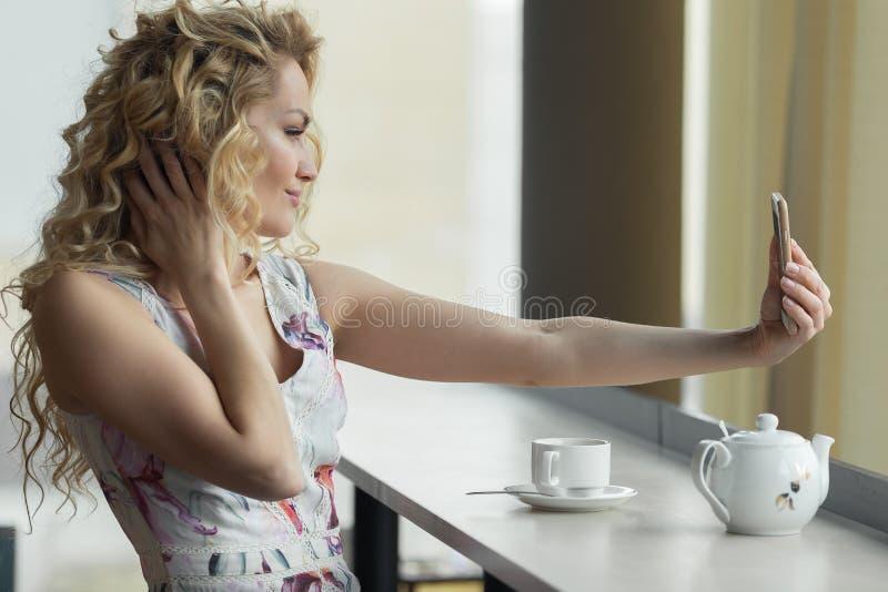 Młoda blondynki dziewczyna robi jaźń portretowi na jej mądrze telefonie obraz stock