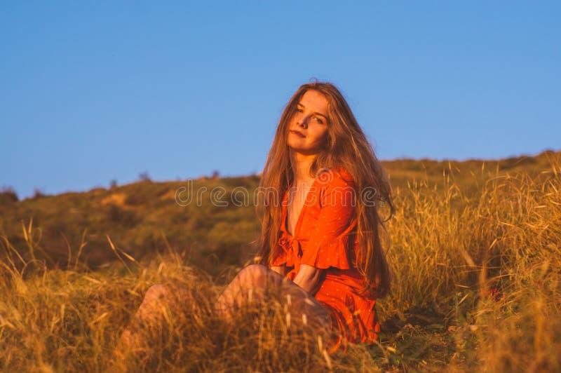 Młoda blondynki dziewczyna w czerwieni sukni obsiadaniu na trawie zdjęcia stock