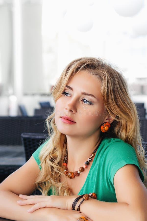 Młoda blondynki dziewczyna w zielonym koszulki i biżuterii obsiadaniu w kawiarni na letnim dniu obrazy royalty free