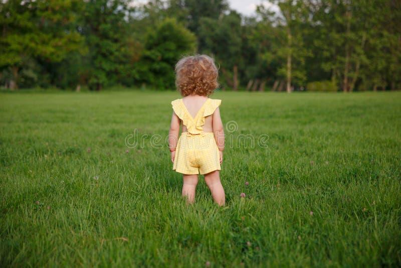 Młoda blondynki dziewczyny pozycja na trawie fotografia royalty free