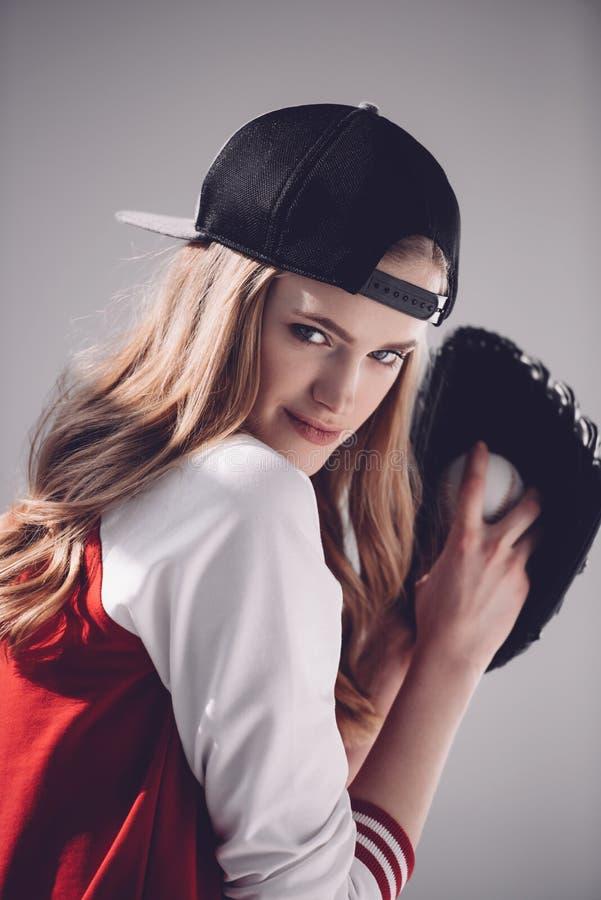 Młoda blondynki kobieta bawić się baseballa i ono uśmiecha się przy kamerą obraz royalty free