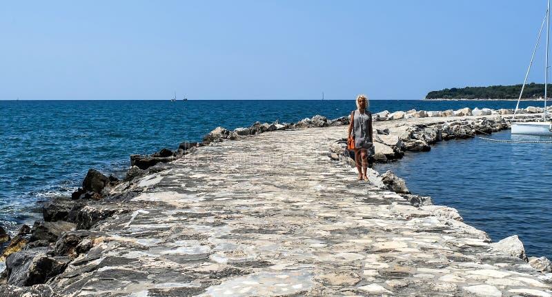 Młoda blondynki kobieta chodzi na dennym molu w odległości zdjęcie royalty free