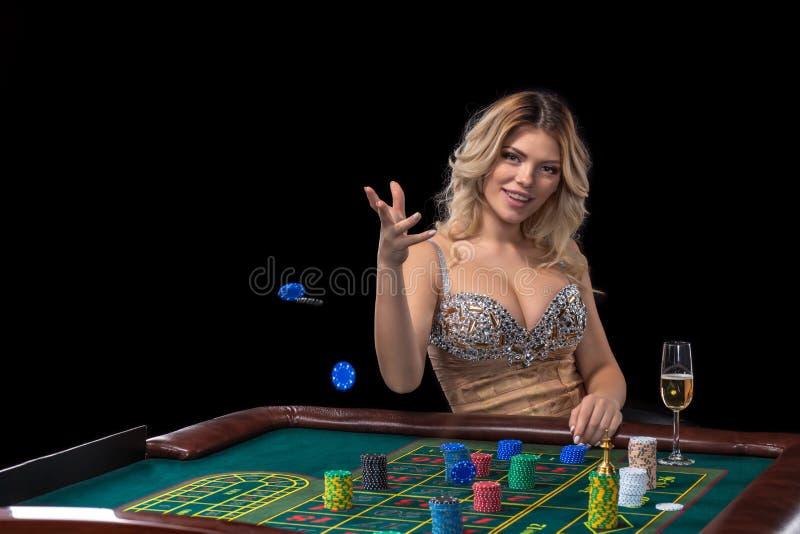 Młoda blondynki kobieta jest ubranym piękną seksowną błyszczącą suknię bawić się ruletę w kasynie fotografia stock
