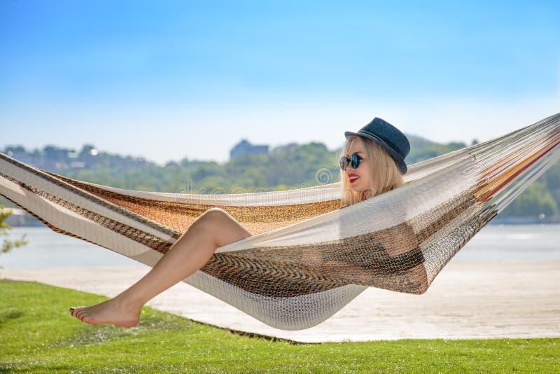 Młoda blondynki kobieta odpoczywa na hamaku obraz stock