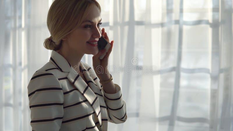 Młoda blondynki kobieta opowiada na telefonie w okno fotografia royalty free