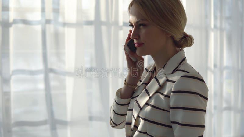 Młoda blondynki kobieta opowiada na telefonie w okno zdjęcie royalty free