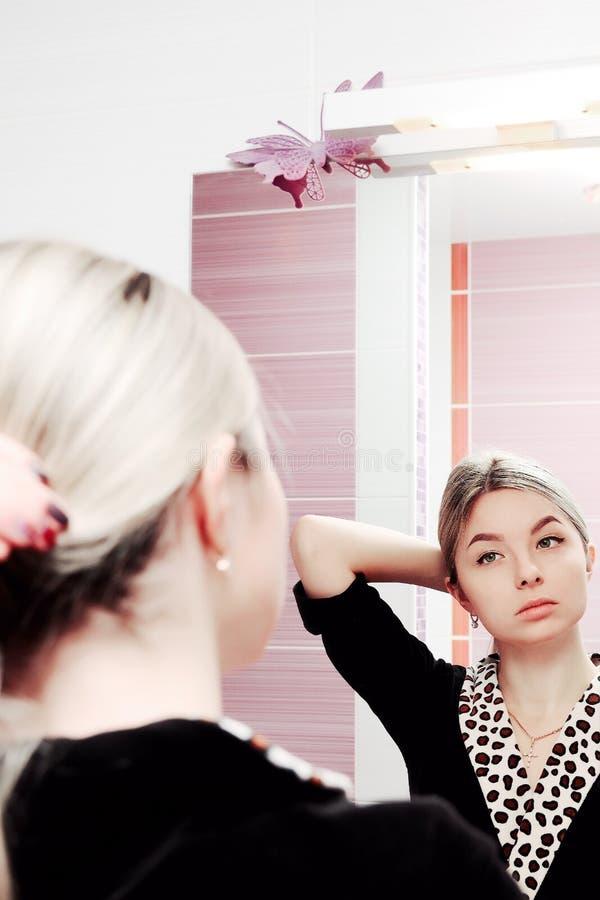 Młoda blondynki kobieta patrzeje odzwierciedlać i czesze jej włosy fotografia royalty free