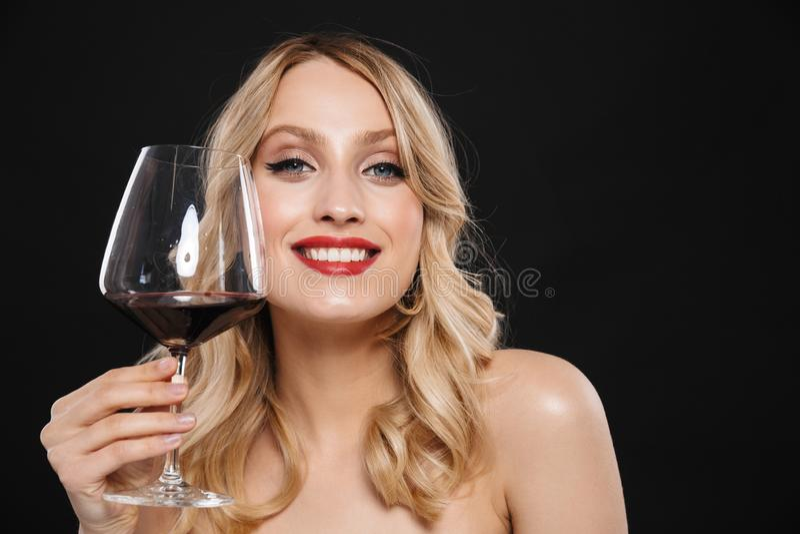Młoda blondynki kobieta pije czerwone wino z jaskrawego makeup warg czerwony pozować odizolowywam nad czerni ściany tłem fotografia royalty free