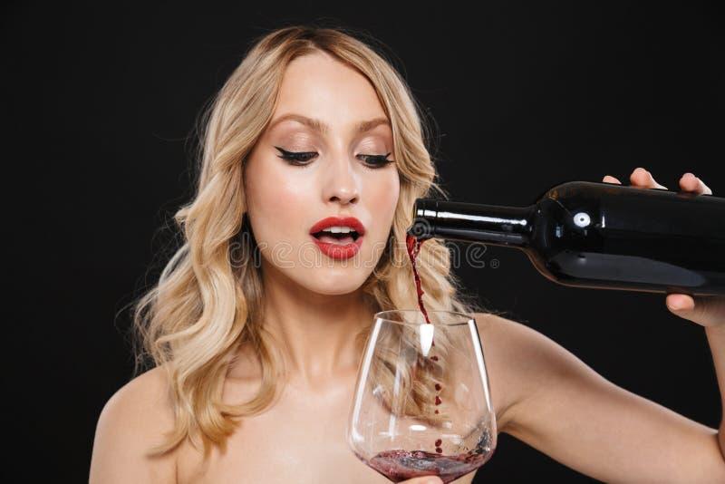 Młoda blondynki kobieta pije czerwone wino z jaskrawego makeup warg czerwony pozować odizolowywam nad czerni ściany tłem obrazy stock