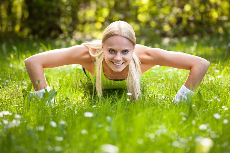 Młoda blondynki kobieta Podnosi Robić Pcha obrazy stock