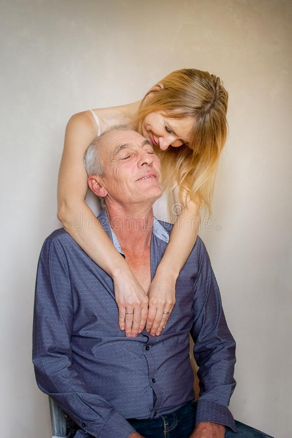 Młoda blondynki kobieta Rozbiera się Jej Starszego męża obsiadanie na krześle na Ściennym tle Para z pełnoletnią różnicą fotografia stock