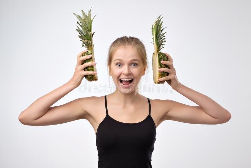 Młoda blondynki kobieta trzyma dwa przyrodniego dojrzałego ananasa na białym tle Jest szczęśliwa i energia pełno zdjęcia stock