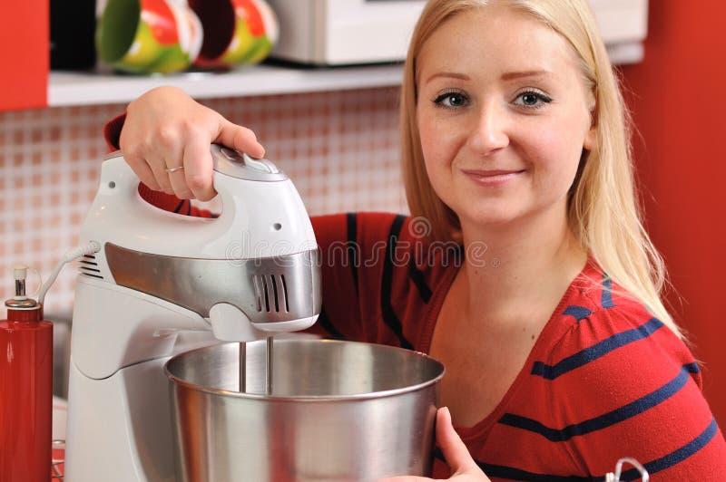 Młoda blondynki kobieta używa melanżer w czerwonej kuchni. zdjęcia royalty free