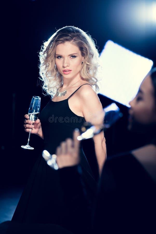 Młoda blondynki kobieta w czerni sukni mienia wina szkle i patrzeć kamerę zdjęcie royalty free