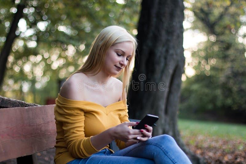 Młoda blondynki kobieta z smartphone obsiadaniem na drewnianej ławce w parku, cieszy się naturę zdjęcie royalty free