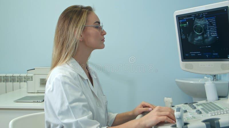 Młoda blondynki kobiety lekarka przegląda ultradźwięku rezultat obrazy royalty free