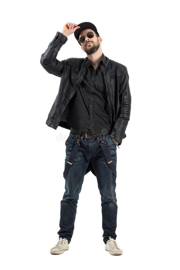 Młoda brodata mężczyzna mienia nakrętka jest ubranym okulary przeciwsłonecznych patrzeje kamerę zdjęcie royalty free