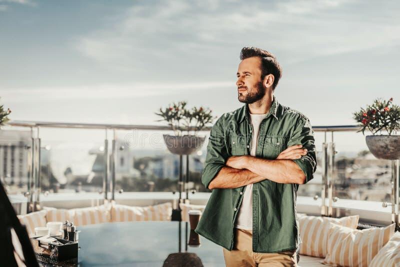 Młoda brodata mężczyzna pozycja przy plenerową kawiarnią zdjęcia stock